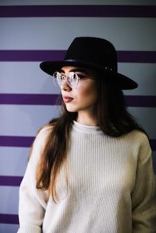 Mujer joven con estilo en sombrero y lentes