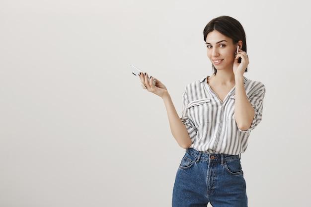 Mujer joven con estilo usando auriculares inalámbricos y teléfono móvil, llamando a clientes