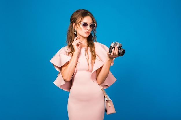 Mujer joven con estilo en vestido rosa de lujo con cámara retro
