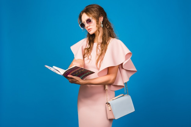 Mujer joven con estilo en vestido rosa de lujo leyendo un libro