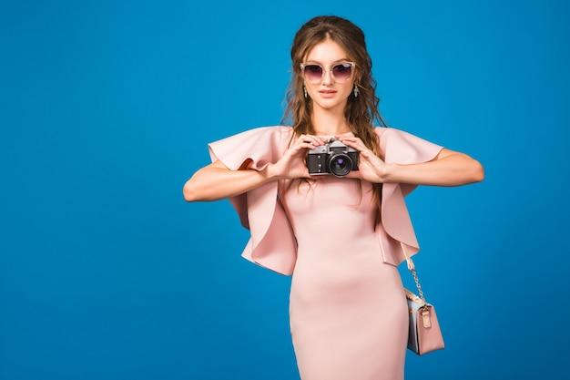 Mujer joven con estilo en vestido rosa de lujo tomando fotografías en cámara vintage