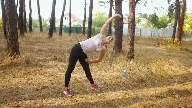 Mujer joven estirando y haciendo ejercicios de fitness en el bosque.