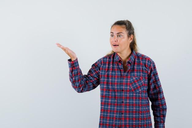 Mujer joven estirando la mano hacia la izquierda sosteniendo algo imaginario en camisa a cuadros y luciendo bonita