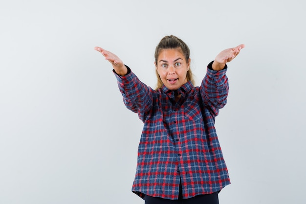 Mujer joven estirando las manos como invitando a entrar en camisa a cuadros y mirando amable