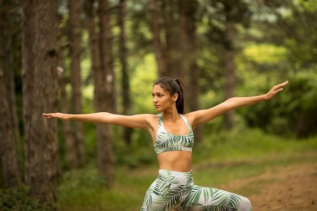 Mujer joven estirando y respirando aire fresco en medio del bosque mientras hace ejercicio