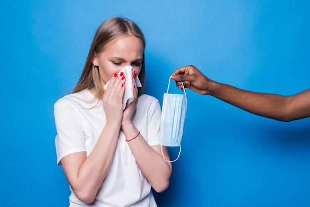 Mujer joven estornuda mientras la mano da máscara médica aislada en la pared azul