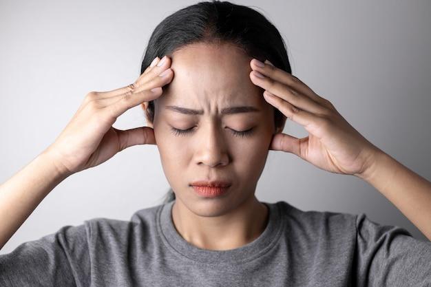 Mujer joven con estrés y dolores de cabeza.