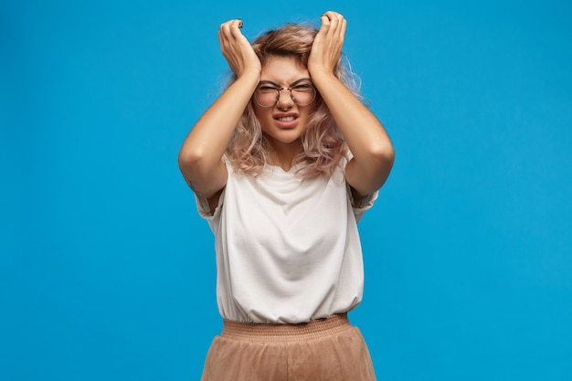 Mujer joven estresada en gafas con estilo apretando la cabeza, no puede soportar un dolor de cabeza intolerable debido a un día estresante en el trabajo. mujer frustrada molesta haciendo muecas de dolor