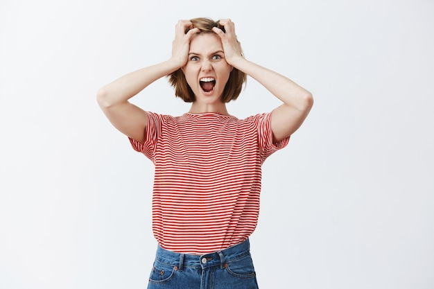 Mujer joven estresada y tensa agarra la cabeza y grita, presa del pánico por algo, luciendo enojada