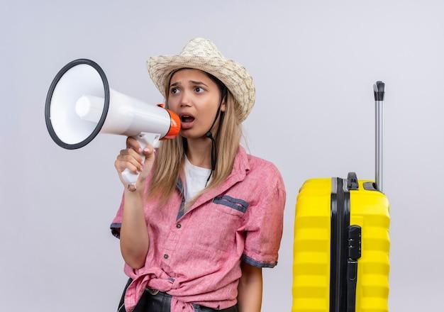 Una mujer joven estresante con camisa roja y sombrero para el sol hablando por megáfono en una pared blanca