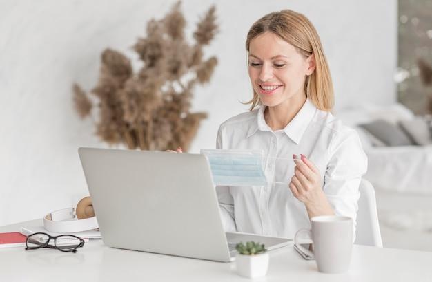 Mujer joven estudiando en la computadora portátil mientras sostiene una máscara médica