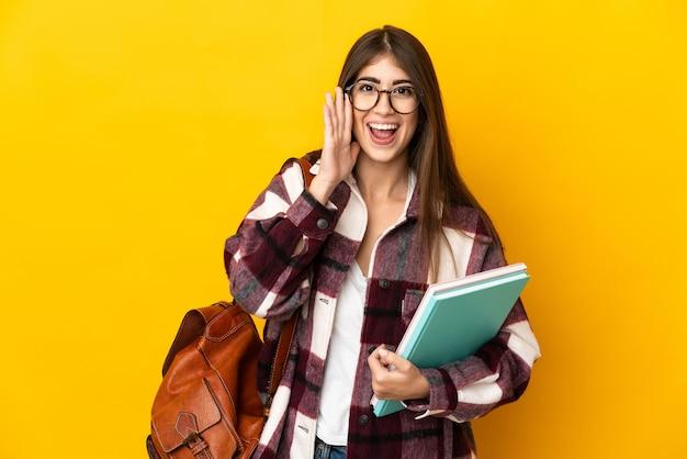 Mujer joven estudiante aislada en la pared amarilla gritando con la boca abierta