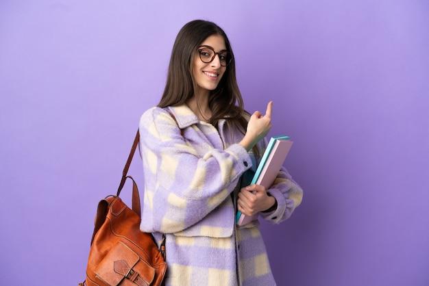 Mujer joven estudiante aislada sobre fondo púrpura apuntando hacia atrás