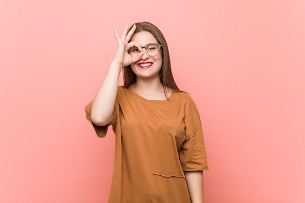 Mujer joven estudiante con anteojos emocionado manteniendo el gesto ok en el ojo.
