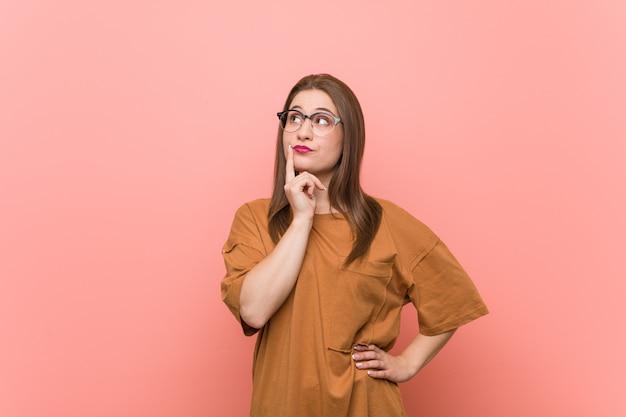 Mujer joven estudiante con anteojos mirando hacia los lados con expresión dudosa y escéptica.