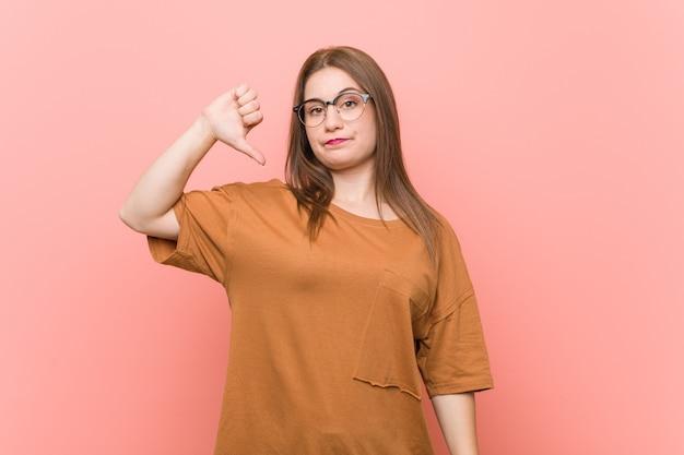 Mujer joven estudiante con anteojos mostrando un gesto de disgusto, pulgares hacia abajo. concepto de desacuerdo