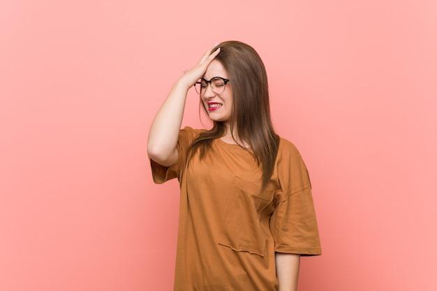 Mujer joven estudiante con anteojos olvidando algo, golpeando la frente con la palma y cerrando los ojos.