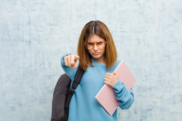 Mujer joven estudiante apuntando hacia adelante con ambos dedos y expresión enojada, diciéndole que cumpla con su deber contra la pared del grunge
