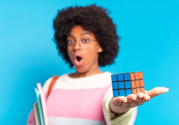 Mujer joven estudiante bastante afro tratando de resolver un problema de inteligencia