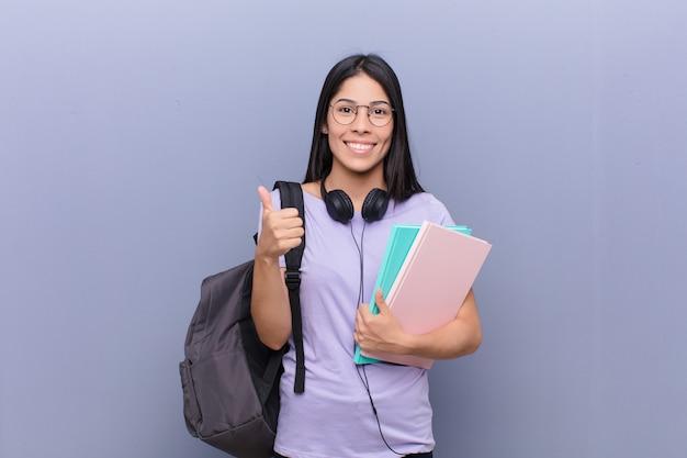 Mujer joven estudiante bastante latino contra la pared gris