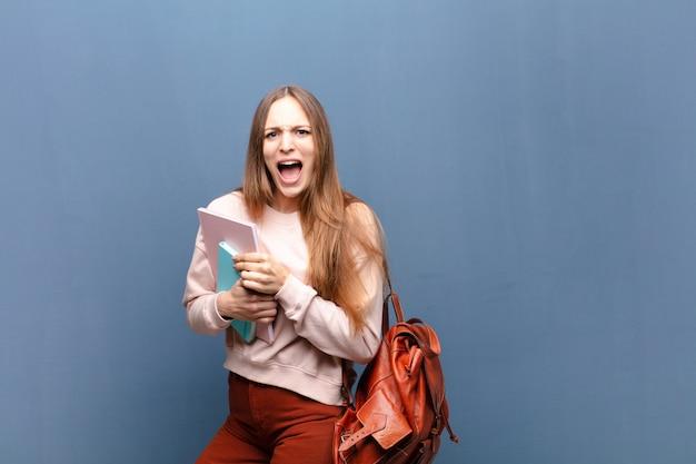 Mujer joven estudiante bonita con libros y bolsa contra la pared azul con un espacio de copia