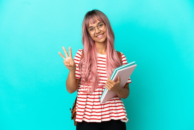 Mujer joven estudiante con cabello rosado aislado sobre fondo azul feliz y contando tres con los dedos
