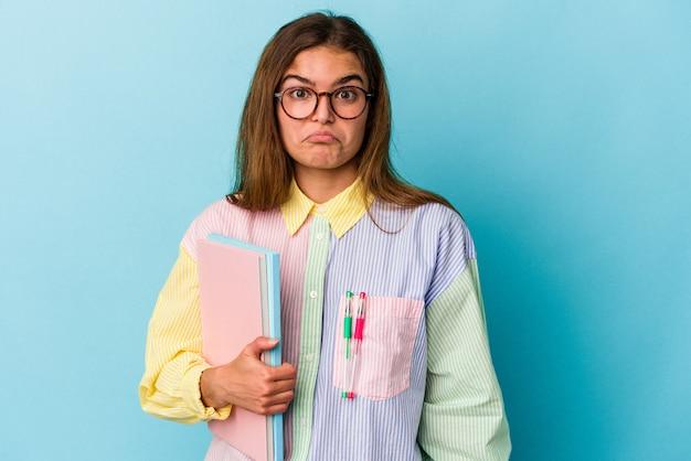 Mujer joven estudiante caucásica sosteniendo libros aislados sobre fondo azul se encoge de hombros y abre los ojos confundidos.