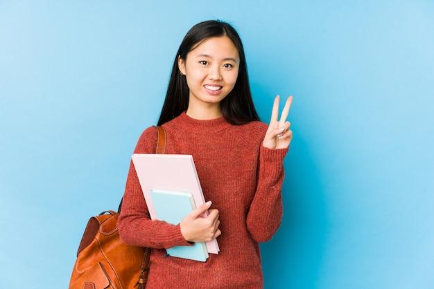 La mujer joven del estudiante chino aisló mostrar el número dos con los dedos.