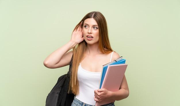 Mujer joven estudiante escuchando algo