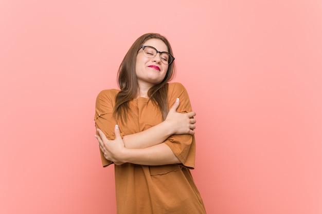 Mujer joven estudiante con gafas abrazos, sonriendo despreocupado y feliz.