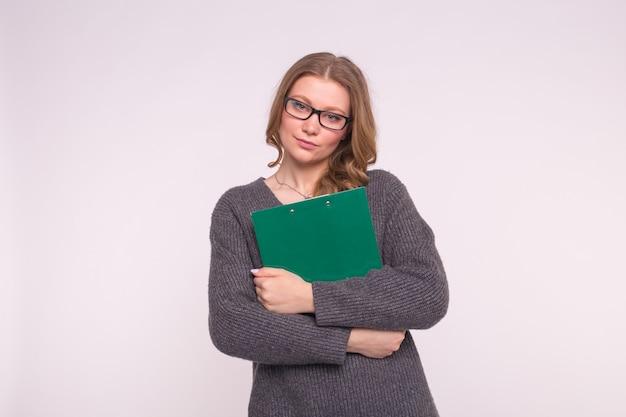Mujer joven estudiante en gafas negras posando con carpeta verde sobre fondo blanco.