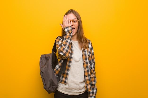 Mujer joven estudiante gritando feliz y cubriéndose la cara con la mano