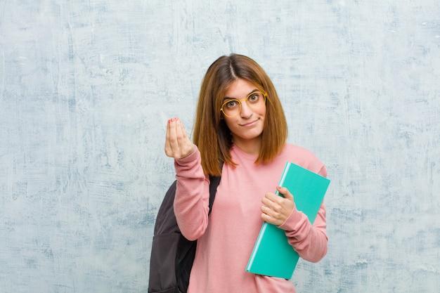 Mujer joven estudiante haciendo capice o gesto de dinero, diciéndole que pague sus deudas.