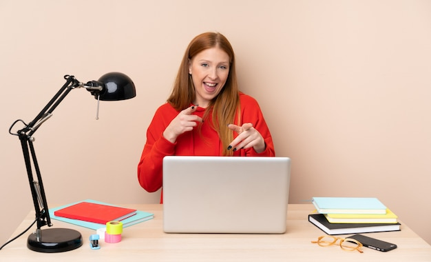 Mujer joven estudiante en un lugar de trabajo con una computadora portátil apuntando hacia el frente y sonriendo