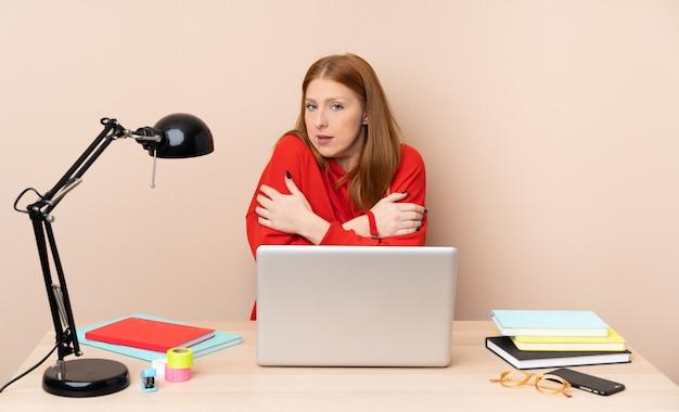 Mujer joven estudiante en un lugar de trabajo con una computadora portátil de congelación