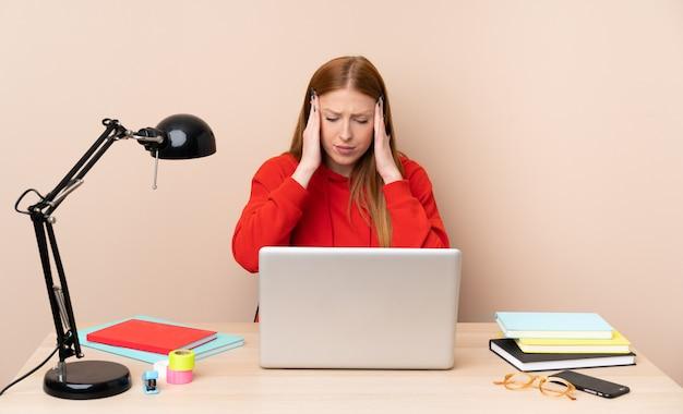 Mujer joven estudiante en un lugar de trabajo con una computadora portátil con dolor de cabeza