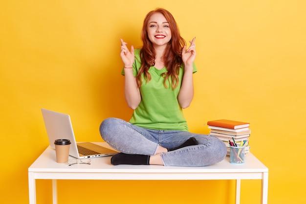 Mujer joven estudiante en el lugar de trabajo con laptop y libros, sentada con los dedos cruzados, desea lo mejor, sentada con las piernas cruzadas sobre la mesa blanca, mira sonriendo directamente a la cámara.