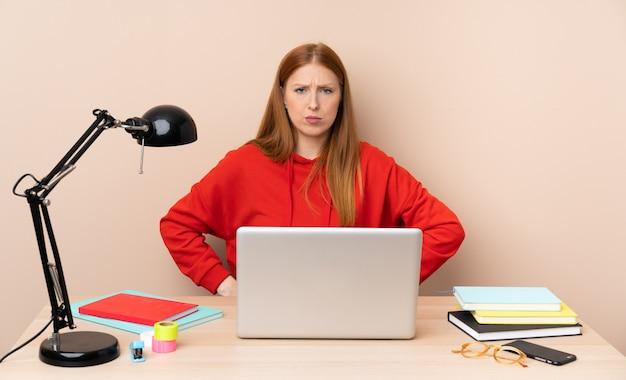 Mujer joven estudiante en un lugar de trabajo con un portátil enojado