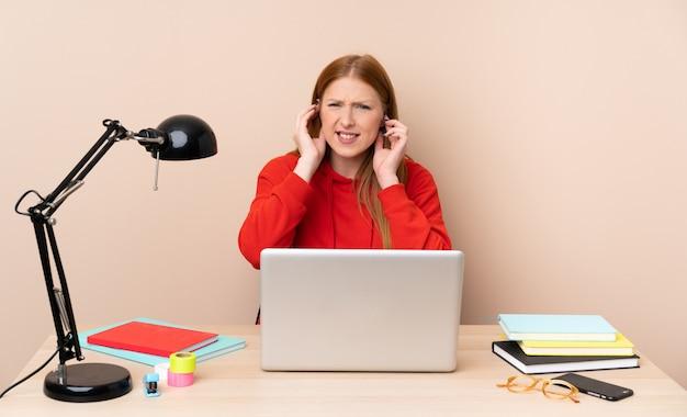 Mujer joven estudiante en un lugar de trabajo con un portátil frustrado y cubriendo las orejas