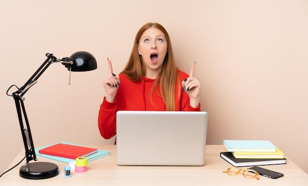 Mujer joven estudiante en un lugar de trabajo con un portátil sorprendido y apuntando hacia arriba