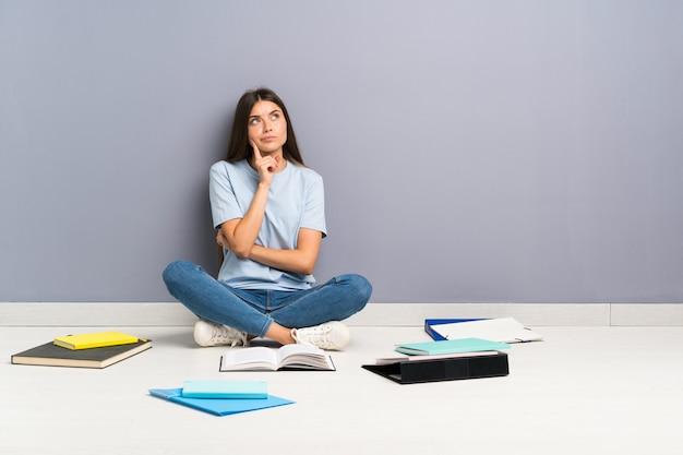 Mujer joven estudiante con muchos libros en el piso pensando en una idea