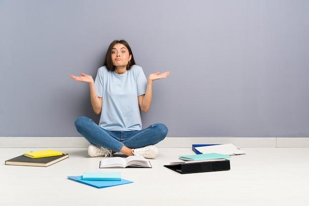 Mujer joven estudiante con muchos libros en el piso que tiene dudas con expresión de la cara confusa