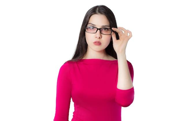 Mujer joven estudiante profesional inteligente en camisa roja tocando gafas con una mano mirando en cámara pensando nueva idea sobre fondo blanco, idea de concepto de mujer de conocimiento