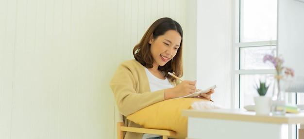 Mujer joven estudiante que estudia el concepto de curso en línea en casa