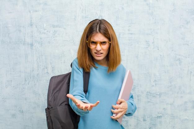 Mujer joven estudiante que parece enojada, molesta y frustrada gritando wtf o qué pasa con tus antecedentes