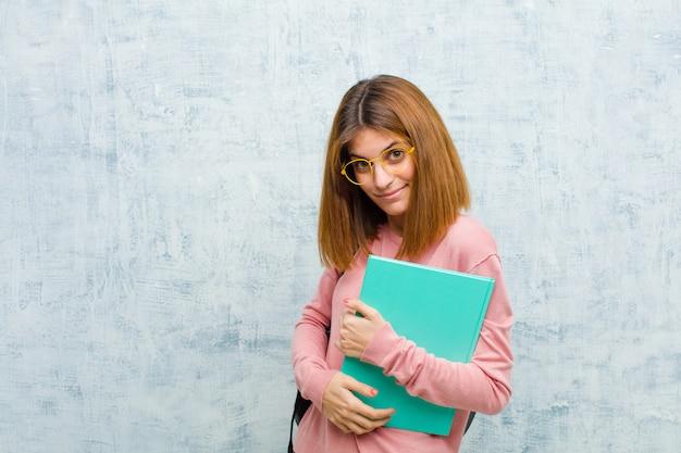 Mujer joven estudiante que parece orgullosa, segura, fresca, descarada y arrogante, sonriente, con éxito en la pared del grunge