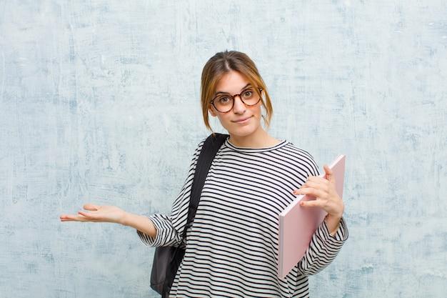Mujer joven estudiante que se siente confundida y confundida, insegura sobre la respuesta o decisión correcta, tratando de tomar una decisión