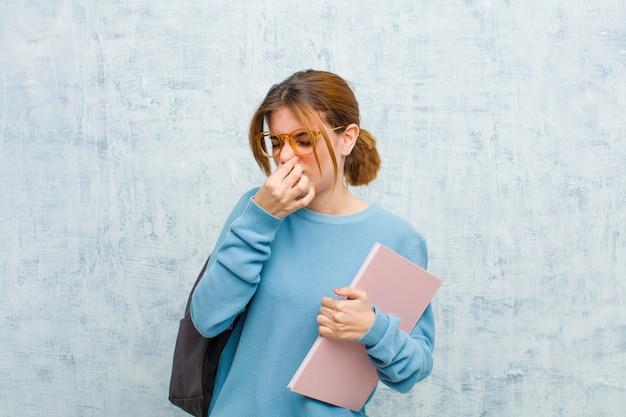 Mujer joven estudiante que se siente disgustada, tapando la nariz para evitar oler un hedor desagradable y desagradable contra la pared del grunge