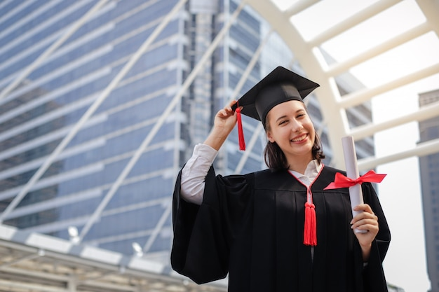 Mujer joven del estudiante que sonríe y que sostiene el papel del certificado del diploma, concepto de la graduación