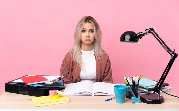 Mujer joven estudiante que trabaja en una mesa triste